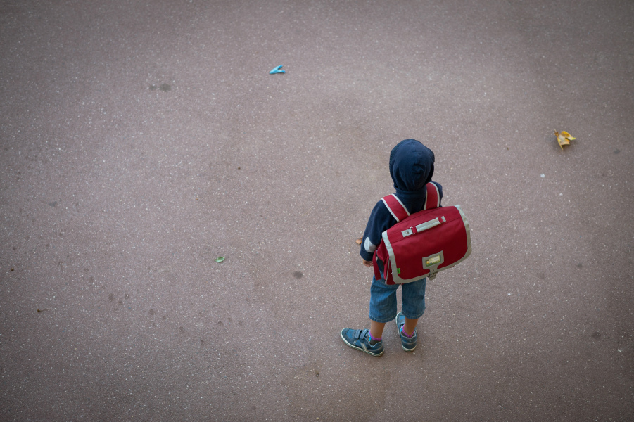 A pupil stands in the courtyard of a primary school on September 3, 2013 in Paris, on the first day of school. More than 12 million pupils went back to school today in France. AFP PHOTO / MARTIN BUREAU  MARTIN BUREAU / AFP