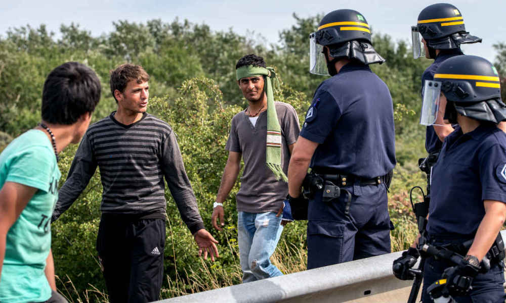 French riot police stand on a road to prevent migrants from reaching the road leading to the ferry port in Calais, northern France, on August 5,2015. The European Commission offered to help France and Britain deal with the migrant crisis at the Channel Tunnel, as police on both sides braced for new attempts at the crossing. A police source said on August 5 some 350 migrants attempted to enter overnight on to the Channel Tunnel site near Calais. AFP PHOTO / PHILIPPE HUGUEN
