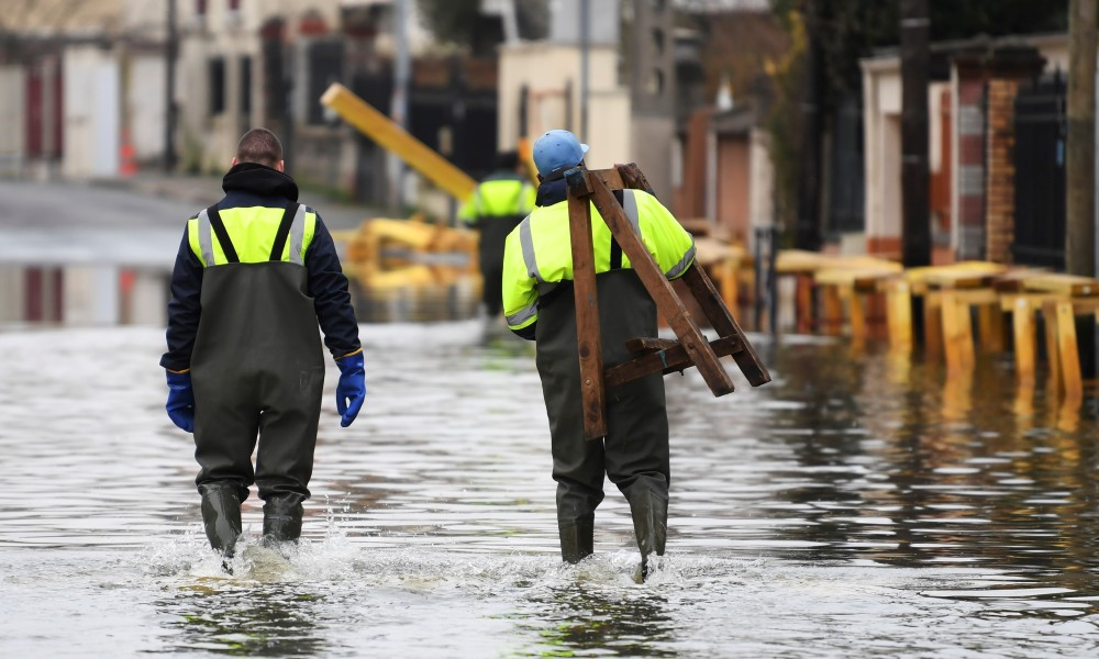 Municipal workers are setting up a makeshit elevated track to help inhabitants reach their home in a flooded street on January 30, 2018, in Villeneuve-Saint-Georges, near Paris. The River Seine peaked on January 29, 2018 at more than four metres above its normal level, heralding a lengthy mop-up job for Parisians after days of rising waters that have put the soggy city on alert.  ALAIN JOCARD / AFP
