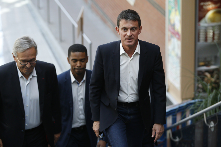 Former French Socialist Prime Minister Manuel Valls (R), escorted by and Evry Socialist mayor Francis Chouat (L) arrives at the Evry City Hall, south of Paris, to cast his vote during the first round of the legislative elections on June 11, 2017.  GEOFFROY VAN DER HASSELT / AFP