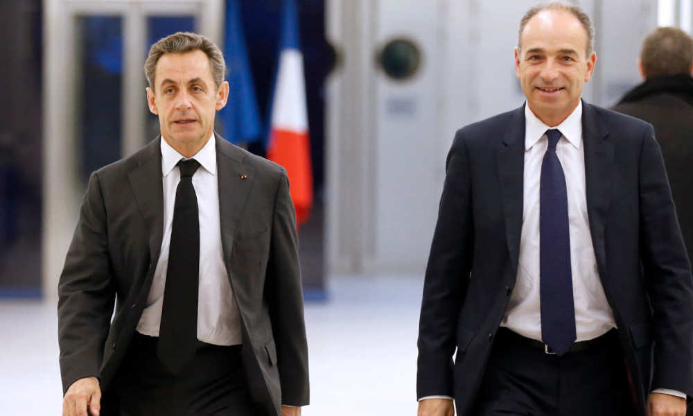 Former president of the French right-wing opposition UMP party Jean-Francois Cope (R) leaves the UMP headquarters in Paris after a meeting with the newly elected head of the UMP and former president of France Nicolas Sarkozy on December 3, 2014.