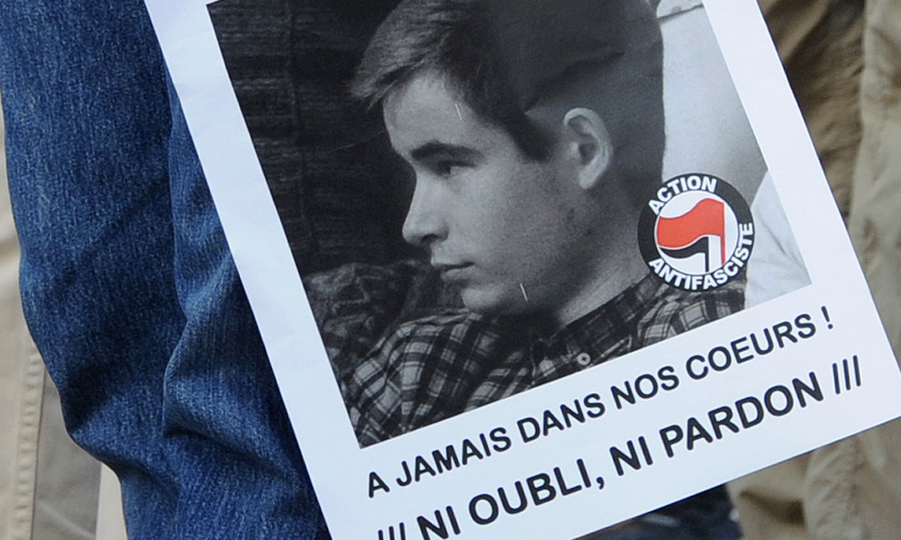 """A demonstrator holds a poster of Clement Meric during a rally on June 6, 2013 in the southwestern town of Toulouse after the young far-left activist was killed during a fight with skinheads in central Paris. Clement Meric, an 18-year-old French far-left activist and student at the city's prestigious Sciences-Po university, died on June 6 following the fight. Clement Meric had been left brain dead after the violence on June 5. The police source said three men and one woman had been held and that the attacker who is thought to have dealt the fatal blow denied having an intention to kill. The board reads : """"Murdered by far-right activists, forever in our hearts, neither forget, nor forgive"""". AFP PHOTO/PASCAL PAVANI PASCAL PAVANI / AFP"""