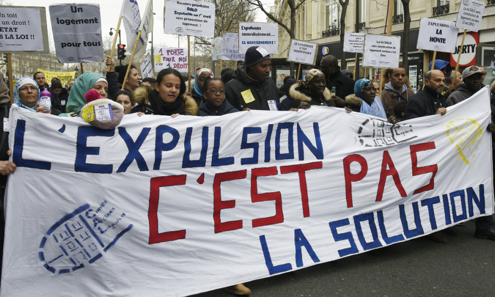 "People hold a banner reading """"Exviction is not the solution"" during a protest on the place de la Republique square in Paris, called by French Right to Housing association (DAL, Droit au Logement) against evictions on April 2, 2016, a day after the end of the winter truce (housing protection during winter months).  DOMINIQUE FAGET / AFP"