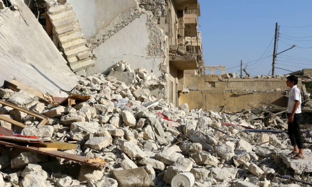 A young Syrian stands looking at the rubble of a collapsed building as rescuers look for victims the following a reported air strike on the rebel-held neighbourhood of Sakhur in the northern city of Aleppo on July 19, 2016. Civilians in rebel-held parts of Syria's Aleppo expressed fears on July 18, 2016 of a lengthy government siege