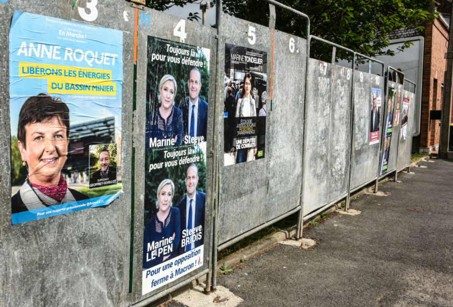 "A picture taken on May 30, 2017 in Henin Beaumont shows election posters for French political Party ""La Republique en Marche"" (REM) and far-right ""Front National"" (FN) candidates ahead of the upcoming French legislative elections.  DENIS CHARLET / AFP"
