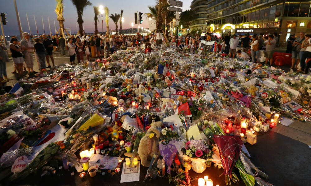 People stand in front of flowers, candles and messages laid at a makeshift memorial in Nice on July 18, 2016, in tribute to the victims of the deadly attack on the Promenade des Anglais seafront which killed 84 people. France was set to hold a minute's silence on July 18, 2016 to honour the 84 victims of Mohamed Lahouaiej-Bouhlel, a 31-year-old Tunisian who drove a truck into a crowd watching a fireworks display on Bastille Day, but a period of national mourning