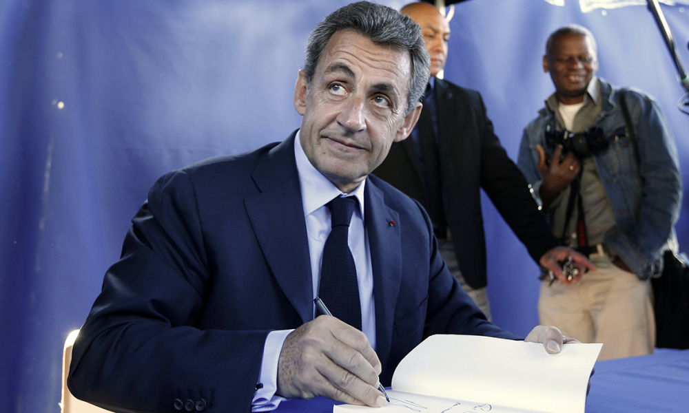 "Former French president and President of France's right-wing Les Republicains (LR) Nicolas Sarkozy signs his book ""La France Pour La Vie"" or ""France for Life"" before a meeting in Nice on April 26, 2016, southeastern France."