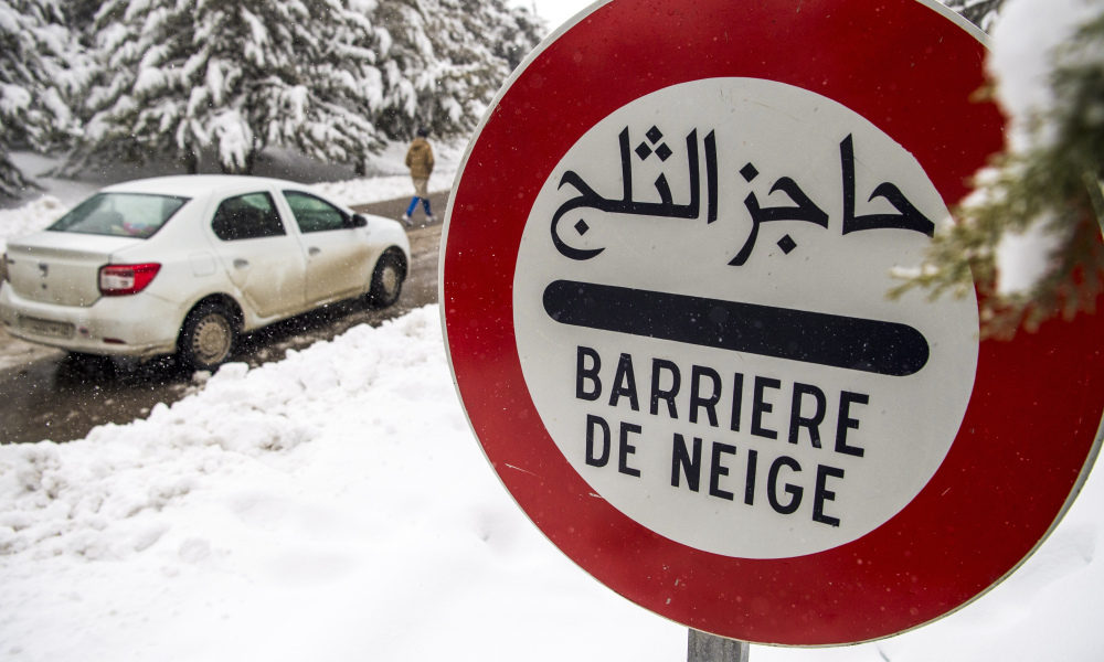 A picture taken on January 21, 2017 shows a street sign warning drivers of a snow bararier on the side of the road in the mountainous Moroccan city of Ifrane on January 21, 2017, as a cold wave hits the North African country.  FADEL SENNA / AFP