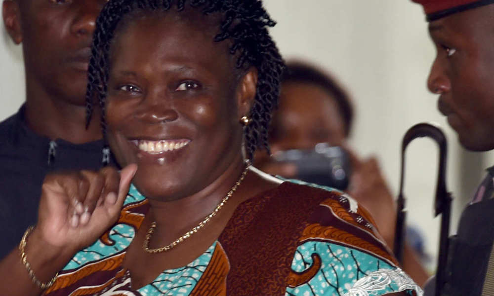 "Ivory Coast's former first lady Simone Gbagbo waves as she arrives at the Court of Justice in Abidjan, on Fevuary 23, 2015 for her trial along with others for ""attempting to undermine the security of the state"" in events leading to a bloody 2010-2011 post electoral crisis that left thousands dead. Gbagbo, who has been held for three years and is also wanted by the International Criminal Court (ICC) for crimes against humanity, is accused with 82 others in this trial viewed as the biggest judicial challenge faced by the post-crisis government of the west African nation. Gbagbo's husband, former president Laurent Gbagbo, who is currently in custody in the Hague, faces four counts of crimes against humanity. AFP PHOTO / ISSOUF SANAGO  ISSOUF SANOGO / AFP"