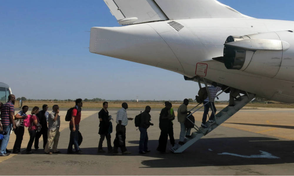 A handout photo released by the UNMISS shows United Nations' non-critical staff boarding a United Nations (UN) plane to be relocate from Juba to Entebbe on December 22, 2103. The United Nations on December 22 said it would