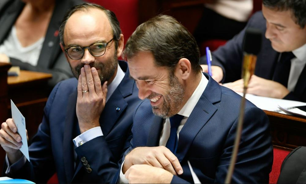 French Prime Minister Edouard Philippe (L) and French Junior Minister for the Relations with Parliament Christophe Castaner smile during a session of questions to the Government on December 12, 2017 at the National Assembly in Paris.  Lionel BONAVENTURE / AFP