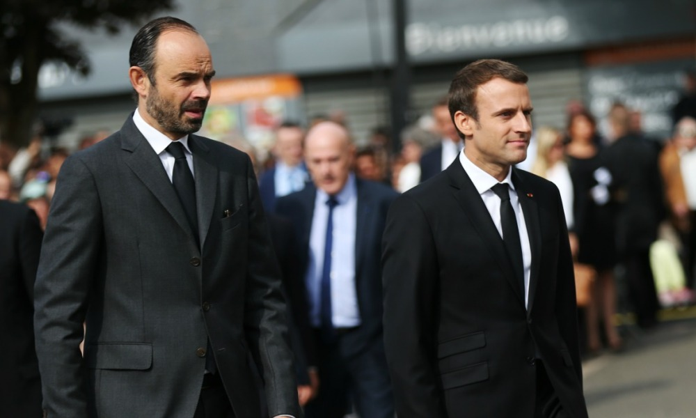 French Prime Minister Edouard Philippe (L) stands next to French President Emmanuel Macron after a mass marking the first anniversary of the killing of a French Catholic priest by two jihadists, outside his church in Saint-Etienne-du-Rouvray, in Normandy, northern France on July 26, 2017.