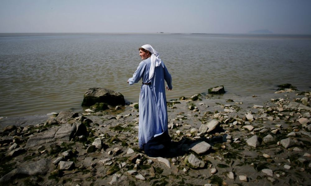 A nun of the Monastic of the Fraternities of Jerusalem cleans her feet in the Manche sea, as she comes back to the Mont-Saint-Michel after a walk, on May 7, 2018.  CHARLY TRIBALLEAU / AFP
