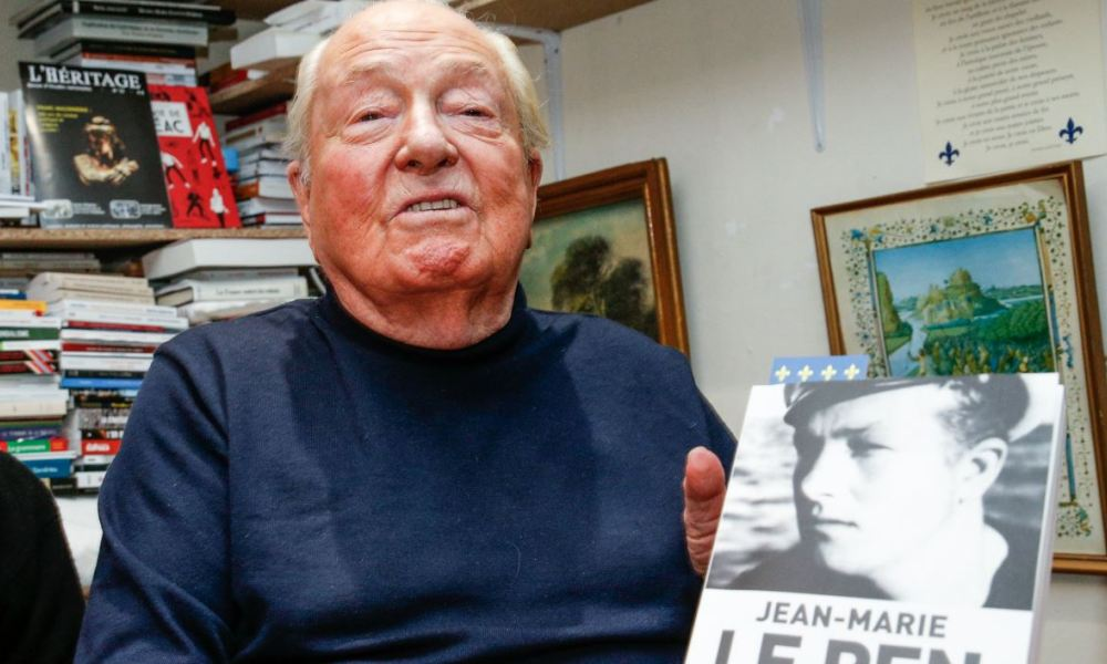 """French far right party Front National honorary president Jean-Marie Le Pen poses with his Memoires' first volume """"Fils de la Nation"""" (son of the Nation) during a book signing at the """"Librairie Francaise"""" book store in Paris on March 10, 2018.  GEOFFROY VAN DER HASSELT / AFP"""