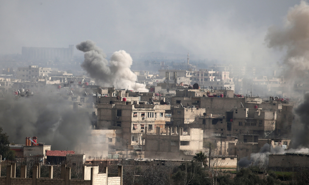 A picture taken on February 20, 2018 shows smoke plumes rising following a reported regime air strike in the rebel-held town of Hamouria, in the besieged Eastern Ghouta region on the outskirts of the capital Damascus.  ABDULMONAM EASSA / AFP