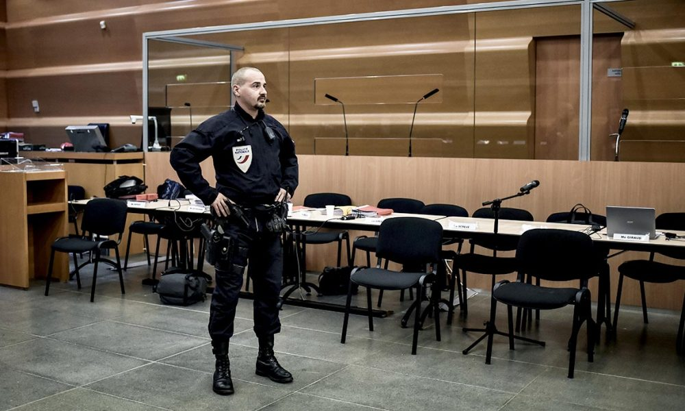 A police officer stands guard in the hearing room that will host a six weeks trial of 12 persons who are accused of Sofiane Tadbirt and Kevin Moubissi murder, on November 2, 2015 at Grenoble courthouse. AFP PHOTO / JEFF PACHOUD  JEFF PACHOUD / AFP