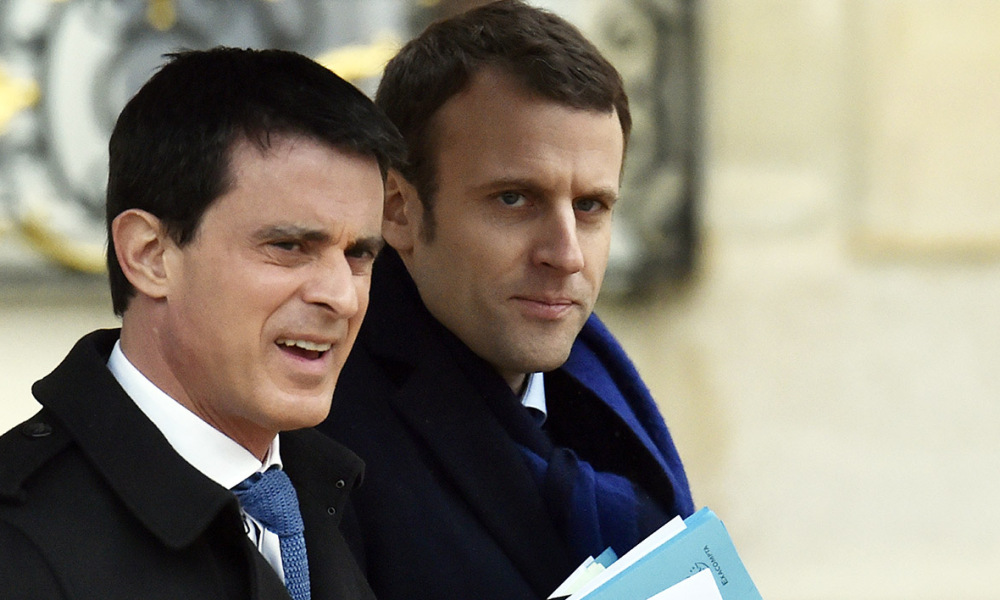 French Prime Minister Manuel Valls (L) and French Economy and Industry minister Emmanuel Macron leave the Elysee palace after the weekly cabinet meeting on March 9, 2016, in Paris. France faces a wave of protests on March 9, 2016, against deeply unpopular labour reforms that have divided an already fractured Socialist government and raised hackles in a country accustomed to iron-clad job security.