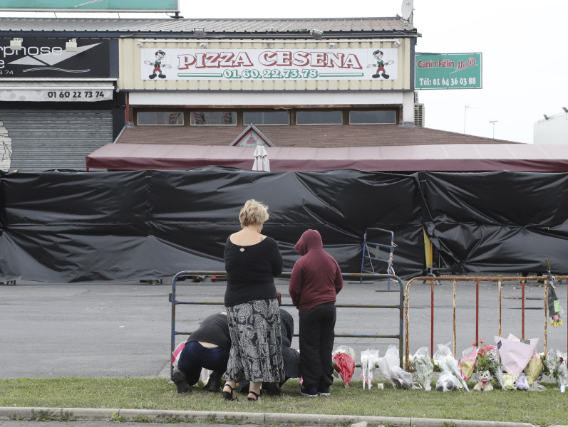 People lay flowers in tribute to the victims on the scene of a car crash, into a pizza restaurant, in Sept-Sorts, 55km east of Paris, on August 15, 2017, resulting in the death of a 13-year-old girl and seriously injuring four.