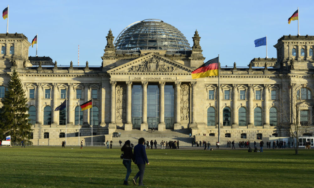 People stand in front of the Reichstag building housing the German parliament Bundestag on December 16, 2013 on the eve of the swearing-in ceremony of the German chancellor and the new cabinet.  John MacDougall - AFP