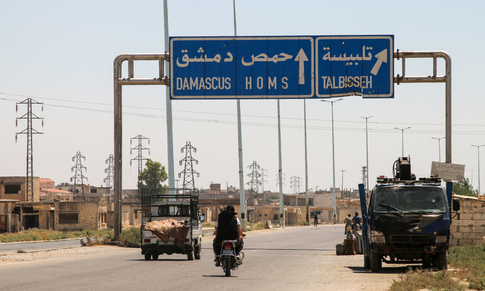 "A picture taken on August 3, 2017 shows vehicles driving past a roadsign that says ""Talbiseh"" in the eponymous central Syrian rebel-held town, north of Homs, along the highway between the capital Damascus and the central city of Homs. A ceasefire between government forces and rebels went into effect in part of central Syria on August 3, 2017 after Russia struck a deal with the opposition on a safe zone in the northern parts of Homs province.  Mahmoud Taha - AFP"