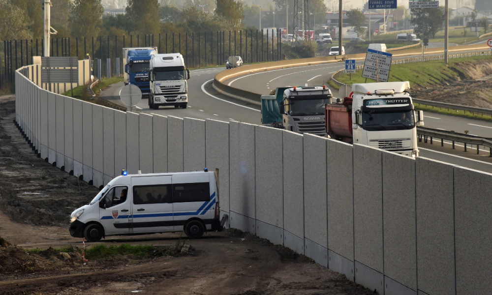 "A picture taken on October 26, 2016 shows a police vehicle next to a concrete 4-metre-high wall in Calais, northern France, dubbed the 'Great Wall of Calais', aimed at preventing migrants and refugees from attempting to reach Britain. Fresh fires broke out on October 26 in the ""Jungle"" migrant camp on the second day of operations to dismantle the squalid settlement in northern France. Smoke billowed over the sprawling camp near Calais for a second day amid fears that abandoned gas cylinders could explode."