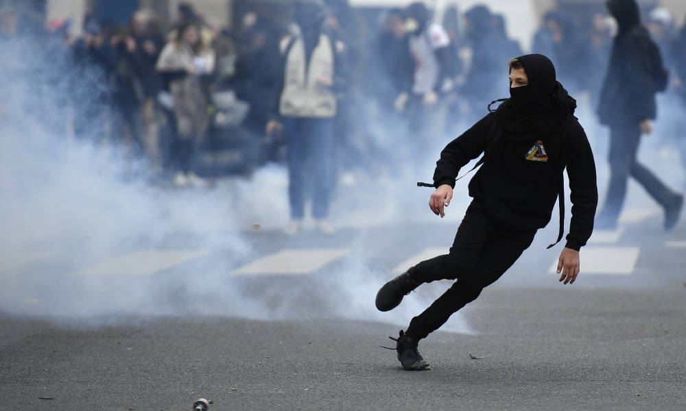 "A young man runs away from tear gas launched by riot police during a protest of students against police brutality, following the alleged rape of Theo, next to the ""Lycee Voltaire"" secondary school in Paris, on February 23, 2017.  Lionel BONAVENTURE / AFP"