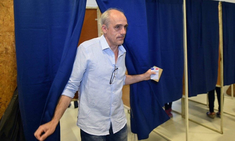 French presidential election candidate for the far-left New Anticapitalist Party (NPA) Philippe Poutou comes out of a voting booth to cast his ballot at a polling station in Bordeaux, central-western France, on April 23, 2017, during the first round of the presidential election.  MEHDI FEDOUACH / AFP