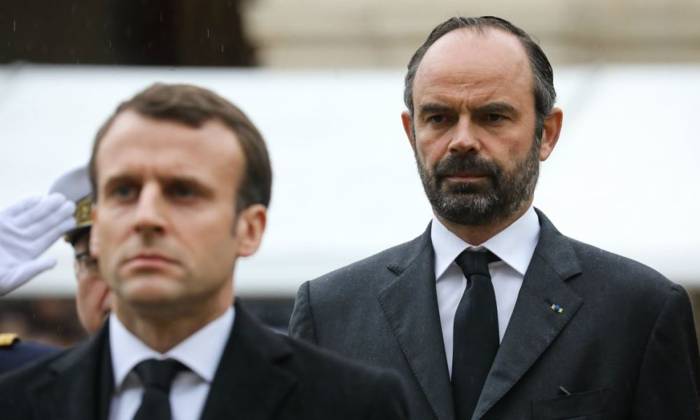 French Prime Minister Edouard Philippe (R) stands behind French President Emmanuel Macron (C), as they attend a national ceremony for Lieutenant-Colonel Arnaud Beltrame, on March 28, 2018 at the Hotel des Invalides in Paris. France honours during a national ceremony on March 28 a heroic policeman who died offering himself as a hostage in a jihadist attack.