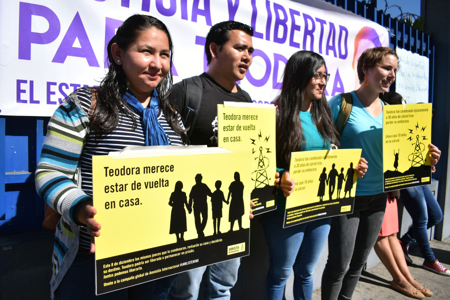 """People demand the release of Teodora Vasquez in front of the Isidro Menendez Judicial Center on December 13, 2017. Salvadorean justice is reviewing on Wednesday, the 30-year prison term, given to Vasquez, after she was found guilty of """"aggravated homicide"""" for a stillbirth in her ninth month of pregnancy. Her lawyer and rights groups call for her to be freed. OSCAR RIVERA / AFP"""