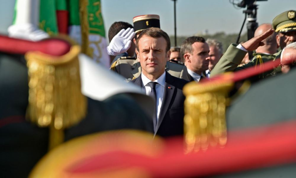 French President Emmanuel Macron reviews the honour guard upon his arrival in Algiers on December 6, 2017.  Ryad KRAMDI / AFP