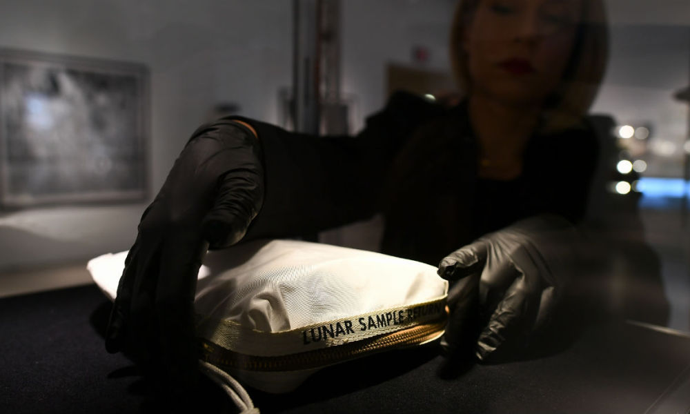 This file photo taken on July 13, 2017 shows Sotheby's Cassandra Hatton as she adjusts the Apollo 11 Contingency Lunar Sample Return Bag, used by Neil Armstrong on Apollo 11 to bring back the very first pieces of the moon ever collected, during a media preview for Space Exploration auction in New York. Jewel Samad - AFP