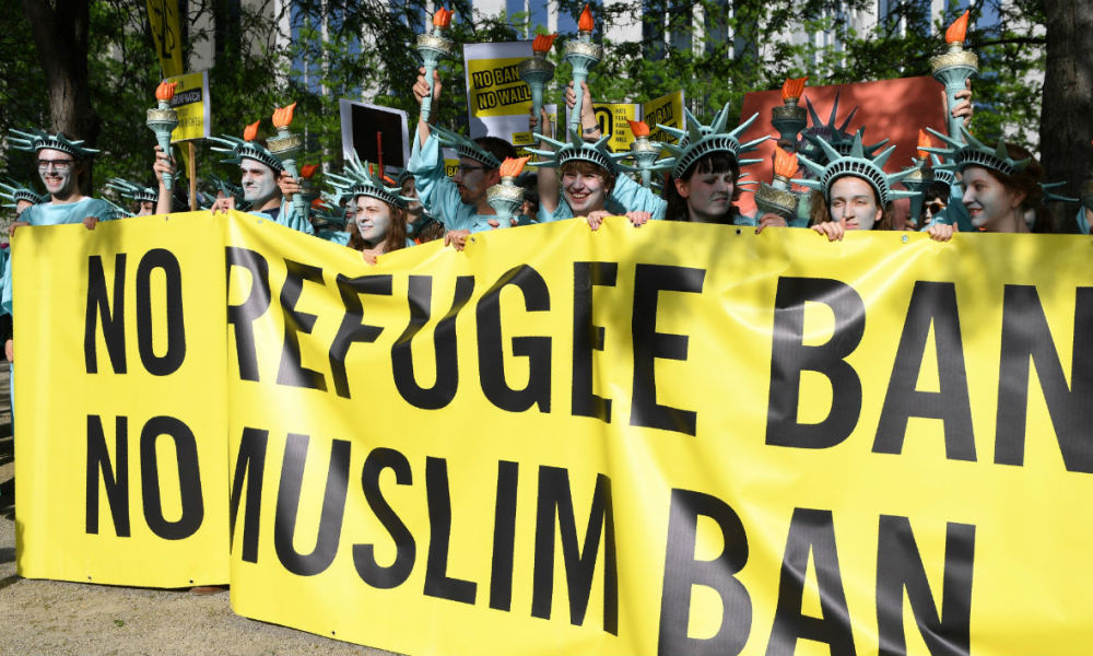 Protesters wearing Statue of Liberty costumes hold a banner reading 'No refugee ban, no Muslim ban' as they take part in a demonstration against the US president in Brussels on May 24, 2017.  US President Donald Trump is on a two-day visit to Belgium, to attend a NATO (North Atlantic Treaty Organization) summit on May 25. ERIC FEFERBERG / AFP