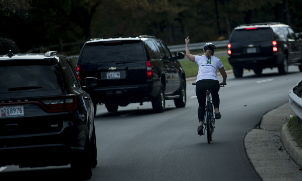 A woman on a bike gestures with her middle finger as a motorcade with US President Donald Trump departs Trump National Golf Course October 28, 2017 in Sterling, Virginia.  Brendan Smialowski / AFP