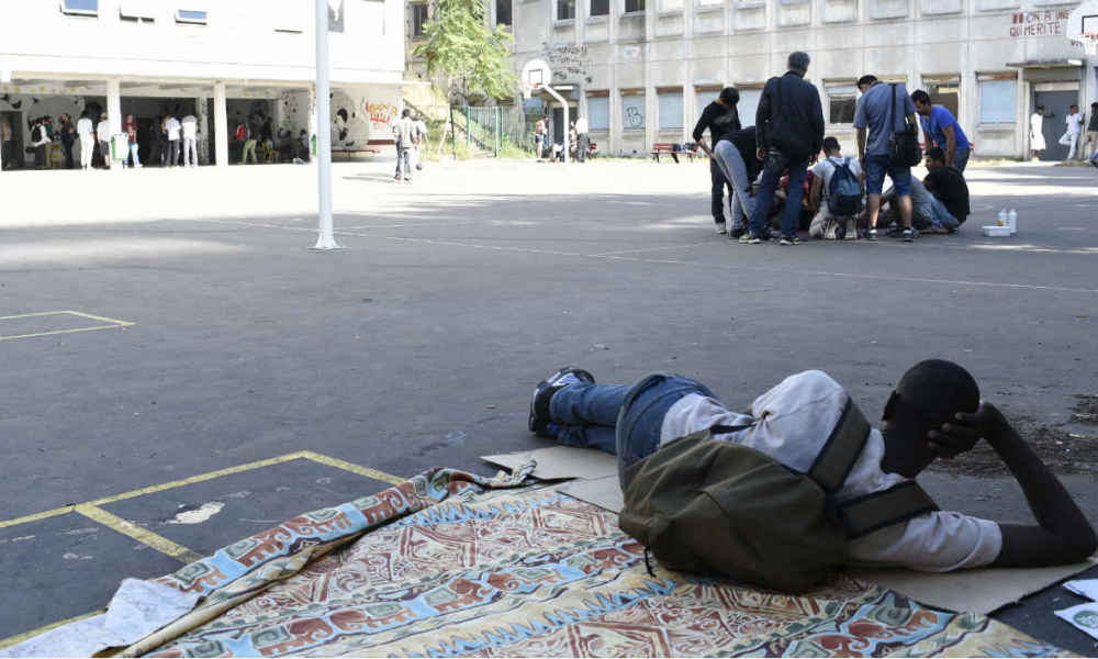 A migrant rests on the basketball court of disused secondary school Guillaume-Bude, in Paris, on August 2, 2015. According to volunteers, around 200 migrants, some of whom were expelled from the camp on Rue Pajol, are currently occupying the annexe of the secondary school in the 19th district of Paris. AFP PHOTO / ALAIN JOCARD