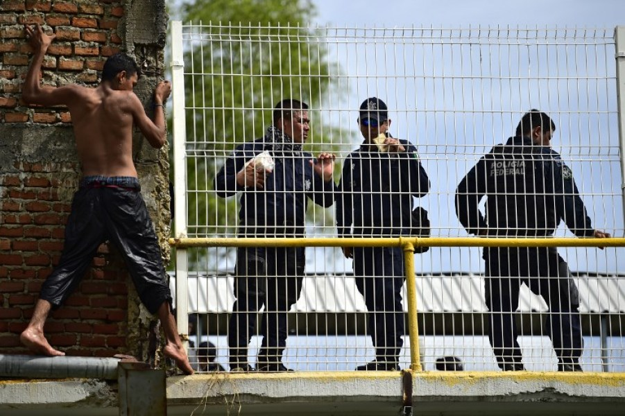 A Honduran migrant heading in a caravan to the US, prepares to jump to the Suchiate River from the Guatemala-Mexico international border bridge, near Mexican Federal Police officers, in Ciudad Hidalgo, Chiapas state, Mexico, on October 20, 2018. Thousands of migrants who forced their way through Guatemala's northwestern border and flooded onto a bridge leading to Mexico, where riot police battled them back, on Saturday waited at the border in the hope of continuing their journey to the United States. Pedro Pardo / AFPvv