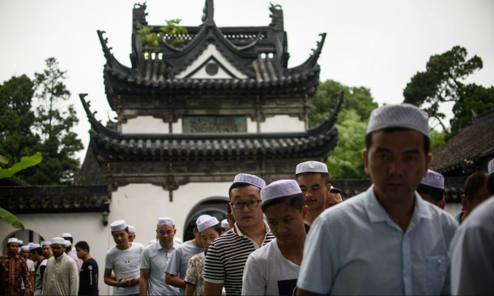 Chinese Muslims leave the garden of the Songjiang Mosque after the Eid al-Fitr prayer in Shanghai on July on July 18, 2015. Muslims around the world are celebrating the Eid al-Fitr festival, which marks the end of the fasting month of Ramadan. AFP PHOTO / JOHANNES EISELE  JOHANNES EISELE / AFP