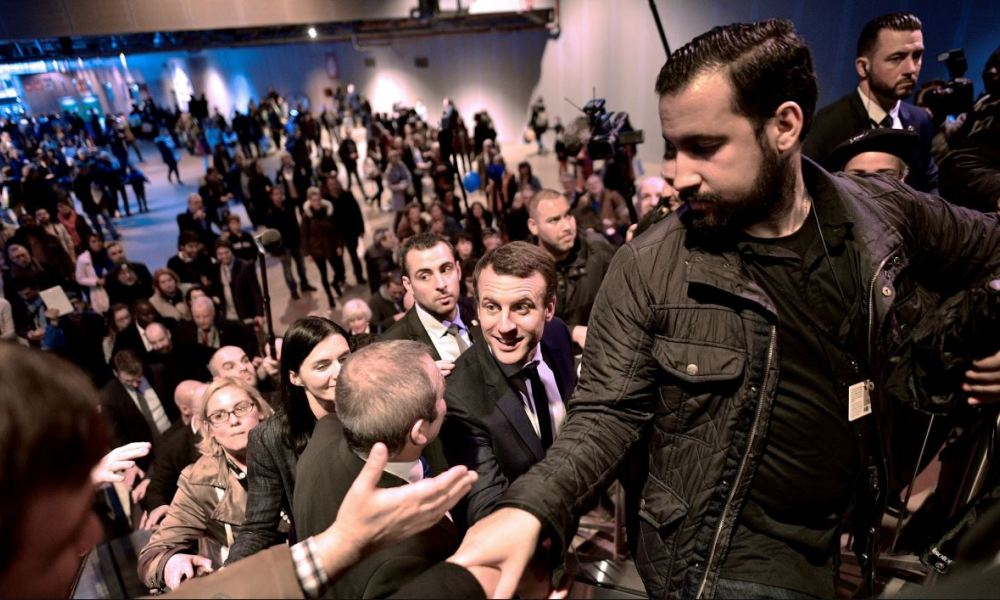 In this file picture taken on March 1, 2017 French presidential election candidate for the En Marche ! movement Emmanuel Macron (C), flanked by head of security Alexandre Benalla (R) shakes hands as he visits Paris' international agriculture fair, in Paris.