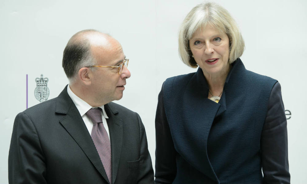 "Britain's Home Secretary Theresa May (R) greets French Minister of the Interior Bernard Cazeneuve (L) in the Home Office, in central London on August 29, 2014. British Home Secretary Theresa May said on August 29 the country's terror threat risk level was being raised to ""severe"" due to fears over the situation in Iraq and Syria. AFP PHOTO / LEON NEAL"