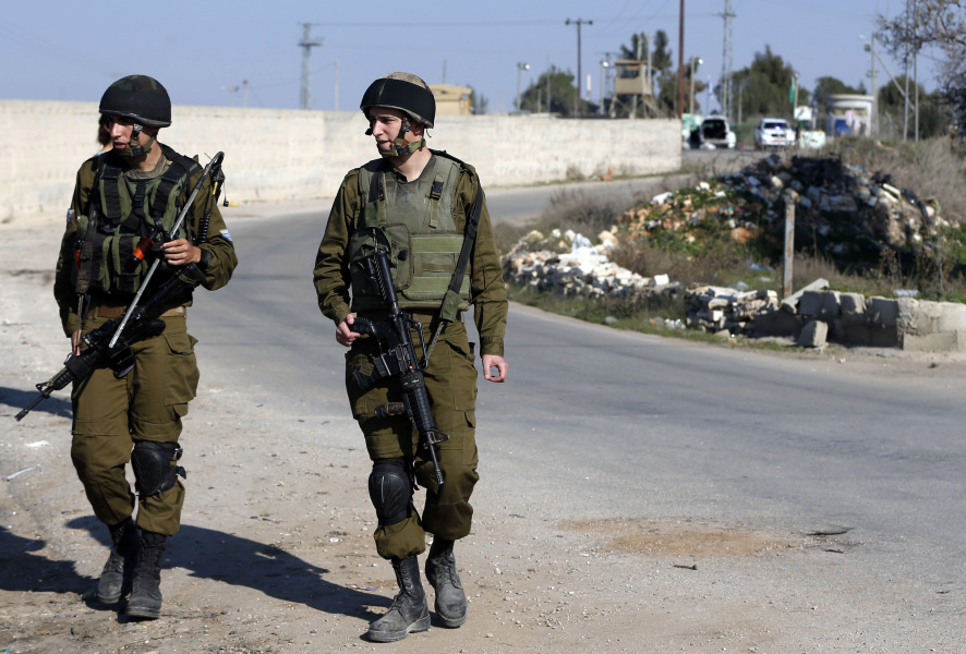 Israeli soldiers stand guard next to the site where a Palestinian man who was shot dead after he reportedly rammed it into a group of Israeli soldiers near a military post in the Israeli occupied West Bank north-east of Jerusalem on December 24, 2015. An Israeli soldier was lightly wounded in the incident, according to the army. AFP PHOTO / AHMAD GHARABLI  AHMAD GHARABLI / AFP