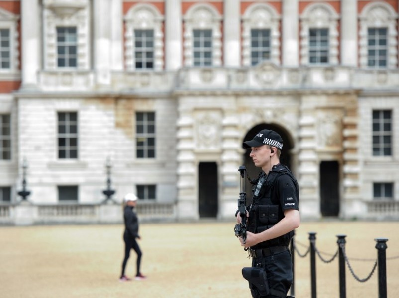 An armed police officer stands guard outside in central London on September 16, 2017.  British police arrested an 18-year-old man on September 16, 2017, in connection to their investigation into the bombing on a packed London Underground train, which injured 30 people. AFP