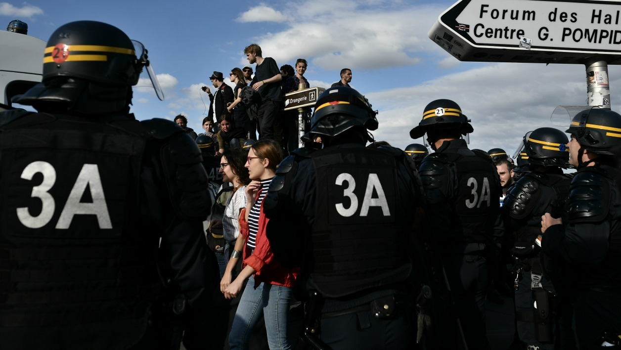 "French CRS anti-riot police stand guard near the French National Assembly building as protesters of the movement dubbed ""Nuit Debout"", or ""Up All Night"", gather for a demonstration against proposed government labour and employment law reforms on July 5, 2016 in Paris. French Socialist Prime Minister Manuel Valls on July 5, 2016 bypassed parliament to force through labour reforms that have sparked four months of strikes and street protests."