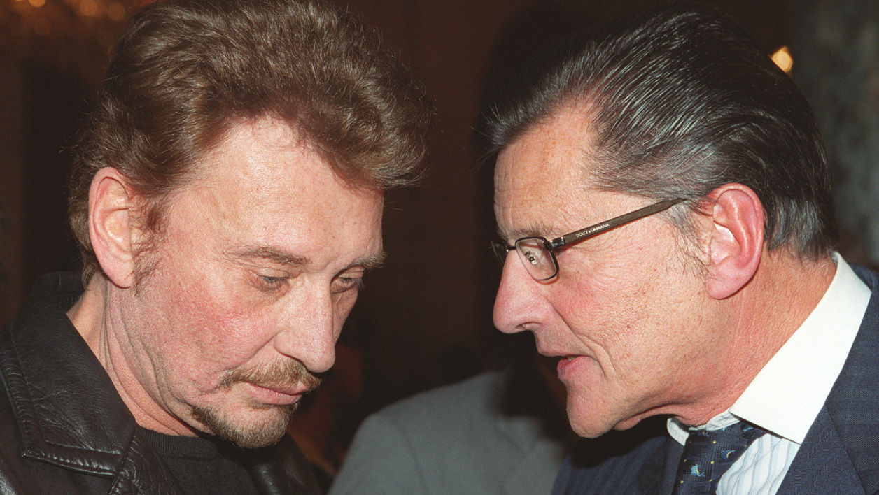 (FILES) This file photo taken on November 16, 1999 shows French singer Johnny Hallyday (L) and his producer Jean-Claude Camus, at the Elysee Presidential Palace in Paris. France's best-known rock star Johnny Hallyday has died aged 74 after a battle with lung cancer, his wife Laeticia told AFP on December 6, 2017. JEAN-PIERRE MULLER / AFP