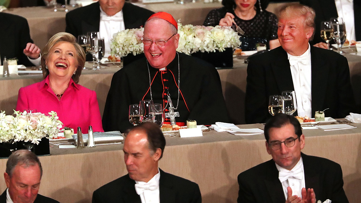 NEW YORK, NY - OCTOBER 20: Sitting between Cardinal Timothy Dolan, Hillary Clinton and Donald Trump attend the annual Alfred E. Smith Memorial Foundation Dinner at the Waldorf Astoria on October 20, 2016 in New York City.The white-tie dinner, which benefits Catholic charities and celebrates former Governor of New York Al Smith, has been attended by presidential candidates since 1960 and gives the candidates an opportunity to poke fun at themselves and each other. Spencer Platt/Getty Images/AFP  SPENCER PLATT / GETTY IMAGES NORTH AMERICA / AFP