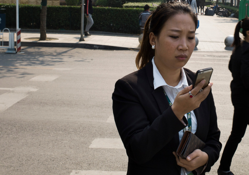 A woman looks at her phone in the Central Business District in Beijing on October 7, 2014. The IMF's analysis and projections of economic developments will present next week the World Economic Outlook. AFP PHOTO / FRED DUFOUR