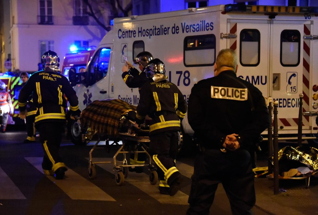 Firefighters evacuate an injured person near the Bataclan concert hall in central Paris, on November 14, 2015. More than 100 people were killed in a mass hostage-taking at a Paris concert hall on November 13 and many more were feared dead in a series of bombings and shootings, as France declared a national state of emergency.  AFP PHOTO / DOMINIQUE FAGET
