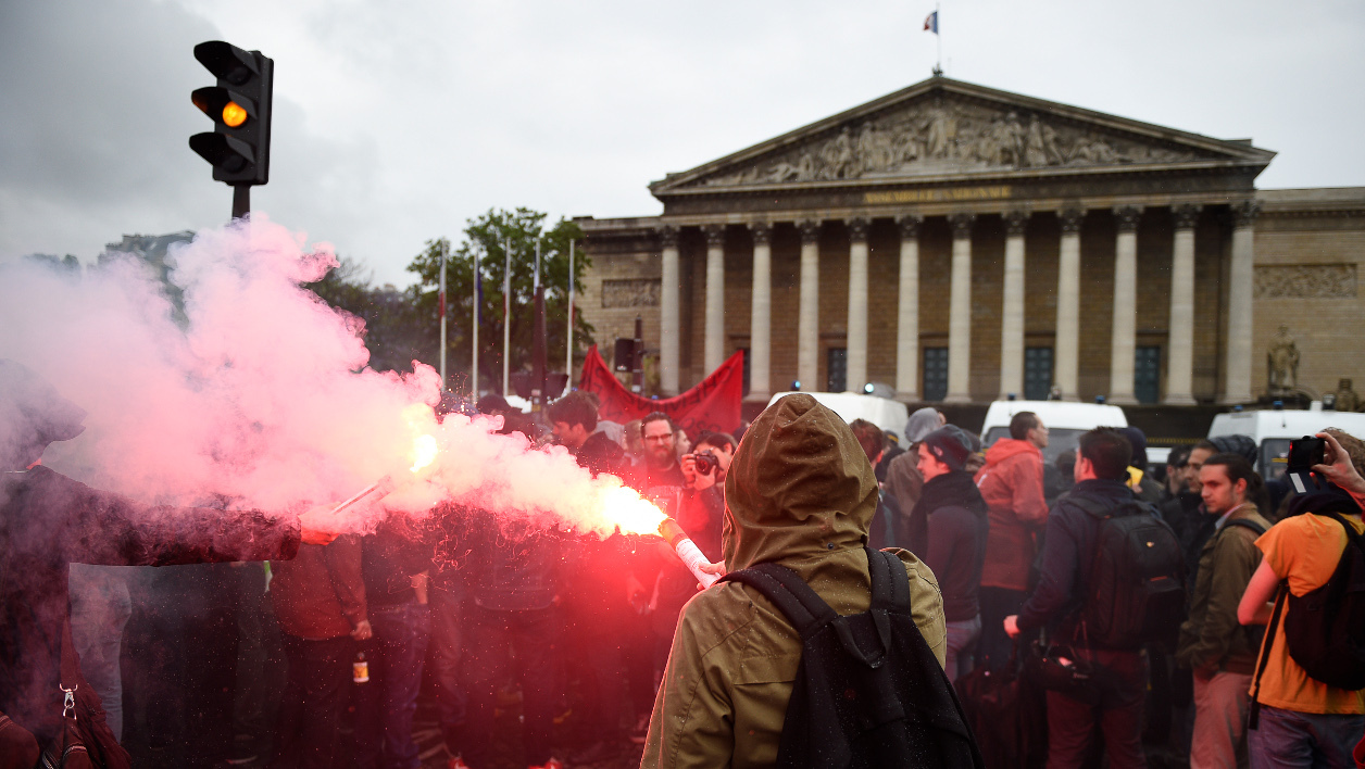 A protester holds a burning flare during a demonstration against the use of the French constitution's Article 49,3, allowing the government to bypass parliament and force through controversial labour reforms, in front of the French National Assembly in Paris, on May 10, 2016. France's Socialist government is to face a no-confidence vote on May 12, 2016, after it bypassed parliament and rammed through a labour reform bill that has sparked two months of massive street protests. AFP PHOTO / MARTIN BUREAU  MARTIN BUREAU / AFP