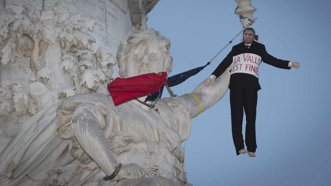"April 10, 2016 shows a dummy representing French Prime Minister Manuel Valls hanged to the ""Statue of the Republic"" during the ""Nuit Debout"" (Up All Night) movement on the Place de la Republique in Paris. The banner reads : ""The waltz is over"", a word play associating the name of Manuel Valls and the waltz dance, written ""valse"" in French. In the heady new world of ""Up All Night"" it was March 41 on Sunday to the people gathered in a main Paris square to share their aspirations for change. It is their way of keeping track of a protest movement that has seen people flock to the Place de la Republique to air their grievances, seek strength in numbers and strategise for a better future every night since March 31. JOEL SAGET / AFP"