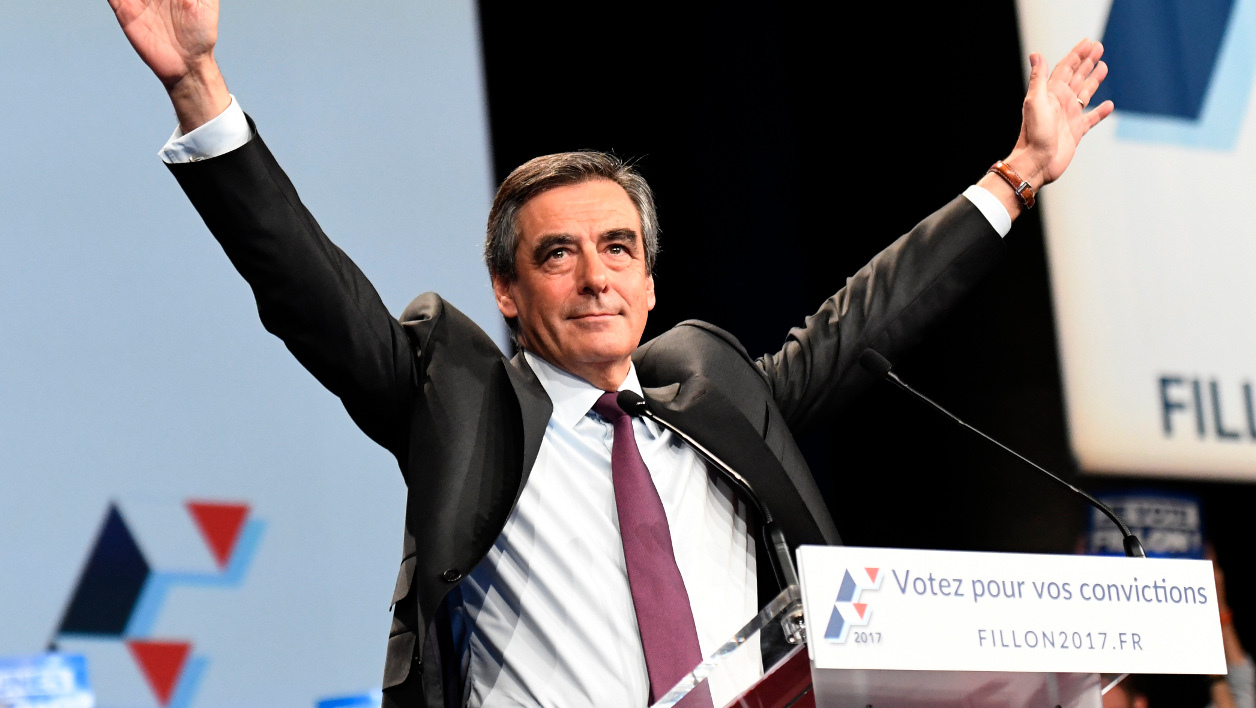 Candidate for the right-wing Les Republicains (LR) party primaries ahead of the 2017 presidential election and former French prime minister Francois Fillon raises his arms as he speaks during a meeting on November 18, 2016 in Paris.  BERTRAND GUAY / AFP