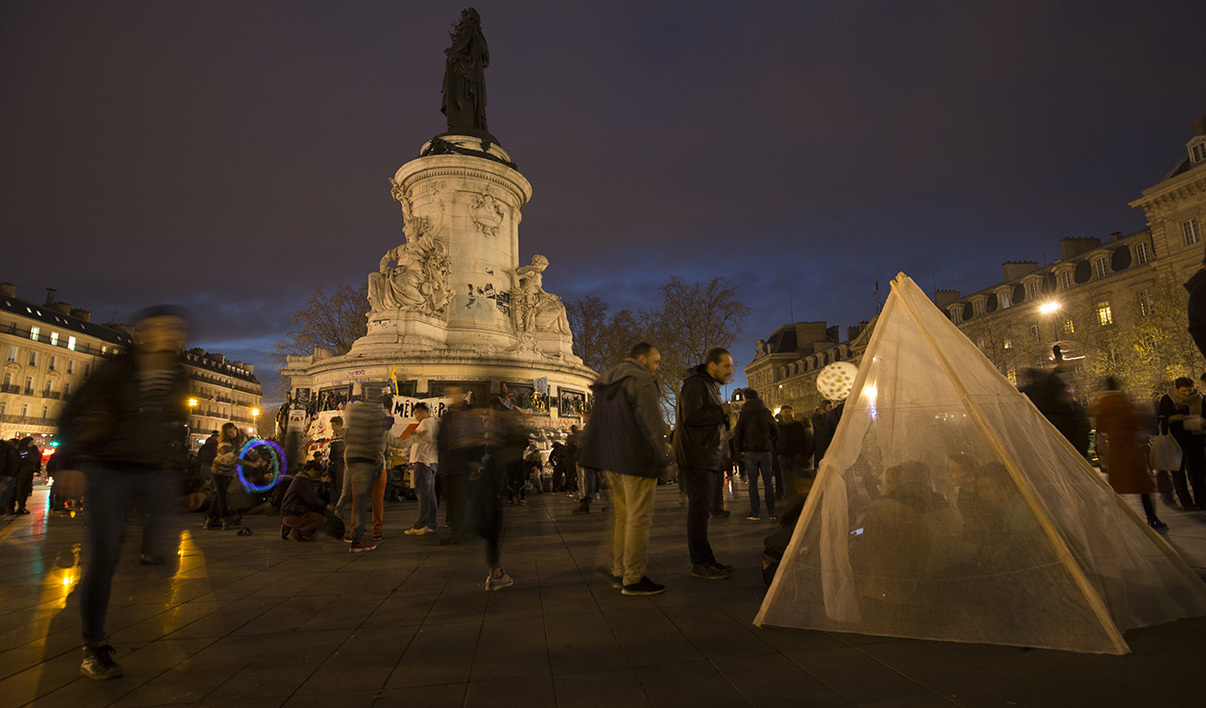 "Participants stroll and sit in a makeshift tent during the ""Nuit Debout"" (Up All Night) movement on the Place de la Republique in Paris on April 13, 2016. The Nuit Debout or ""Up All Night"" protests began in opposition to the Socialist government's labour reforms seen as threatening workers' rights, but have since gathered a number of causes, from"