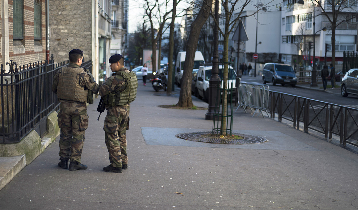"French soldiers patrol on January 14, 2015 in front of a school in Paris, as France announced an unprecedented deployment of thousands of troops and police to bolster security at ""sensitive"" sites following last week's jihadist attacks in Paris.The alert level in shell-shocked France remained at its highest possible as the interior minister announced the deployment of nearly 5,000 police to guard Jewish schools and places of worship."